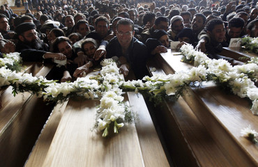 Egyptian Coptic Christians grieve over coffins during mass funeral for seven victims of sectarian clashes, at Samaan el-Kharaz Church in Manshiet Nasr shantytown in eastern Cairo