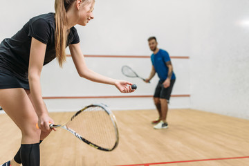 Couple play squash game in indoor training club