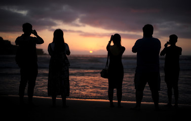 Beachgoers gather at Sydney's Bondi Beach to photography the first sunrise of 2017 following new year celebrations in Australia's largest city