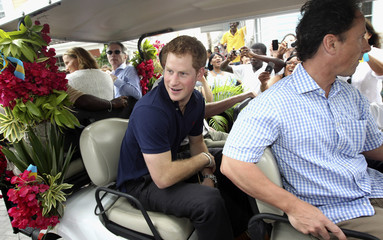 Britain's Prince Harry sits in a specially decorated golf buggy during a tour of Harbour Island in Nassau
