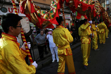 A woman in her work clothes takes pictures during a parade to celebrate the Chinese Lunar New Year of the Rooster in Madrid