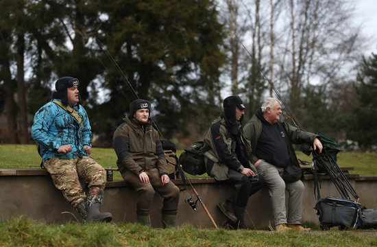 Anglers sit on on a wall after fishing on the opening day of the salmon fishing season on the River Tay at Kenmore in Scotland,