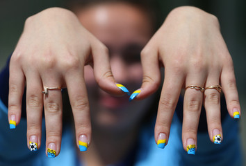 A volunteer shows her nails painted with the colours of the Ukrainian flag and some drawings related to the Euro 2012 ouside the Metalist stadium in Kharkiv