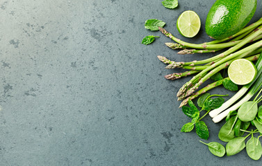 Assorted Green Vegetables and Herbs on stone background