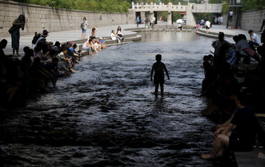 A boy stands ankle deep in the Cheonggye stream as others soak their feet in it while cooling off underneath a bridge during a hot summer day in Seoul