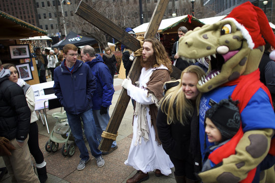 """While visitors pose for photographs with a Santa Claus dinosaur,  Michael Grant, 28, """"Philly Jesus,"""" walks through the Christmas Village in LOVE Park towards the nativity scene after carrying this 12 foot cross 8 miles through North Philadelphia"""