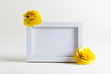 Blank white picture frame with flowers