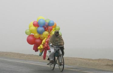 A balloon salesman rides a bicycle during a foggy day in Lahore