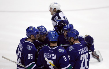 The Vancouver Canucks celebrate Samuel Pahlsson's goal against the Winnipeg Jets while Jets Bryan Little kneels in the background during the third period of their NHL hockey game in Vancouver.