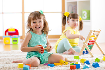 Children toddler and preschooler girls play logical toy learning shapes, arithmetic and colors in kindergarten or nursery