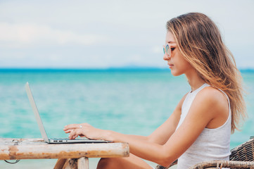 Young sexy woman using laptop on the beach. Freelance work