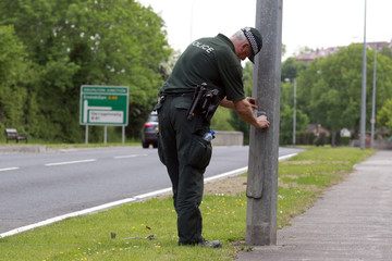 A Police Service of Northern Ireland officer seals a lampost along the road to the Lough Erne Golf Resort where the G8 summit will be held next week, in County Fermanag
