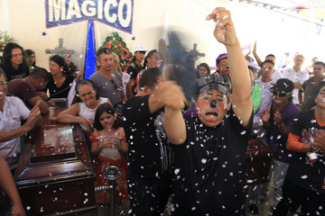 Friends and family look on as a magic show is performed as a tribute during the funeral of Montano and Norena, two cousins and circus clowns who were killed by an armed gang, at Comuna 1 in Cali
