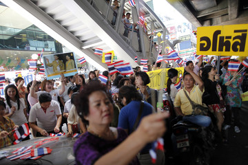 Pro-government protesters wave flags and hold pictures of Thailand's King Bhumibol Adulyadej as they gather at Bangkok's Silom financial district
