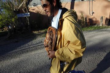 Adan Aguilar carries a wooden carving of Jesus as he makes a pilgrimage to El Santuario de Chimayo in Chimayo