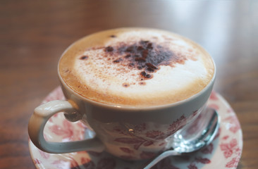 A cup of latte / caffe latte in vintage style. A latte is a coffee drink made with espresso and steamed milk.
