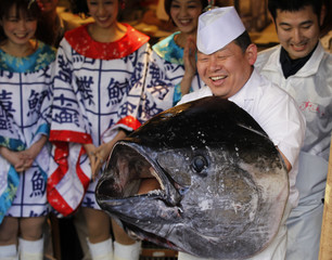 A chef holds the head of a bluefin tuna after cutting its meat at a sushi restaurant in Tokyo