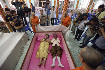 People take pictures and Buddhist monk chants as a groom and a bride lay inside a pink coffin during their wedding ceremony at Wat Takien temple in Nonthaburi province