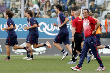 Italy's coach Prandelli walks on the field as his players run during a training session in Modena