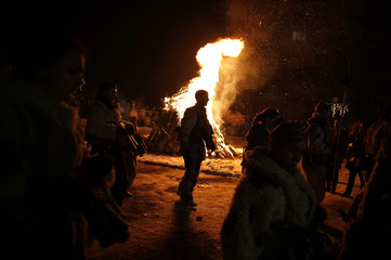 """Men dressed in animal costumes called """"kuker"""" dance in front of a bonfire during a festival in the village of Batanovtsi"""