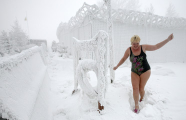 A member of a local winter swimmers' club walks to bathe in the Yenisei River