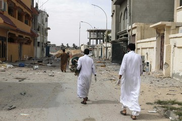 Volunteers walk as they search for dead bodies in the city of Sirte