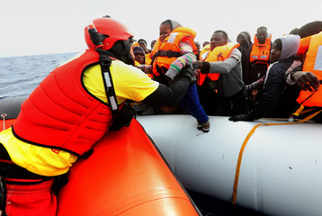 A lifeguard pulls a migrant child to a rescue craft  from an overcrowded raft, as lifeguards from the Spanish NGO Proactiva Open Arms rescue all 112 on aboard