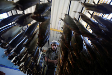 Palestinian man prepares salted fish to be sold in a market ahead of the Eid al-Fitr holiday, in the southern Gaza Strip