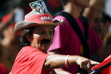 A supporter of Venezuela's President Nicolas Maduro wearing a moustache, which depicts him, and a hat with a picture of Venezuela's late President Hugo Chavez, attends a meeting marking International Women's Day, at Miraflores Palace in Caracas