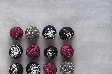 Various fitness bites, raw chocolate truffles from above on gray background. Copy space