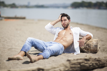 young sexy man on a beach,shallow depth of field