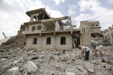 People salvage belongings from the rubble of a house destroyed by a Saudi-led air strike in Yemen's capital Sanaa