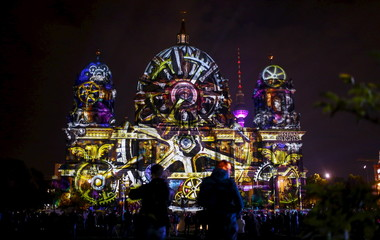 """People look at a light installation at the Berlin Cathedral during the opening day of the """"Festival of Light"""" show in Berlin"""