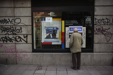 An elderly man uses an ATM machine in Madrid