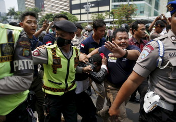 Police detain a protester following a brief clash at a rally to commemorate the West Papuan declaration of independence from Dutch rule in Jakarta