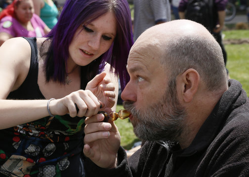 A participant at the 4/20 marijuana holiday smokes a pipe in Civic Center Park in downtown Denver