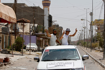 Shiite fighters gesture in Falluja, Iraq, after government forces recaptured the city from Islamic State militants