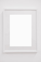 Closeup vertical blank white frame on white wall, decoration concept