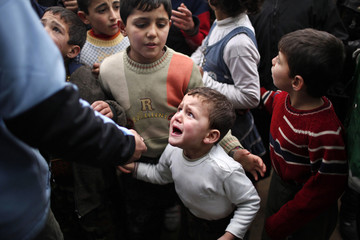 A Syrian child refugee cries as he stands at a queue waiting to receive aid from Turkish humanitarian agencies at Bab al-Salam refugee camp in Syria near the Turkish border