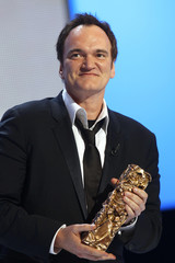 Tarantino smiles as he holds his award during the 36th Cesar Awards ceremony in Paris