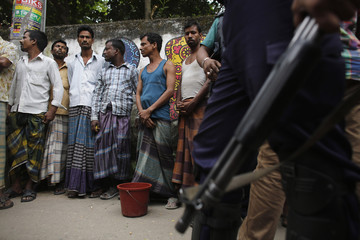 A police officer holds his gun while guarding people detained after an explosion inside a building under construction, during a strike in Dhaka