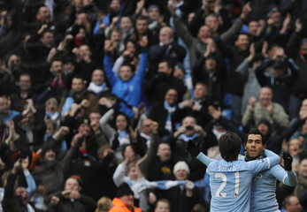 Manchester City's Tevez celebrates scoring with Silva against Notts County during their FA Cup soccer match at Manchester