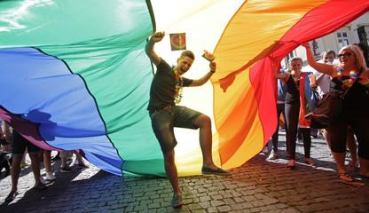 A participant dances underneath a rainbow-colored flag during the Prague Pride Parade in Prague's city centre