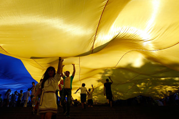 People hold a giant Ukrainian flag as part of celebrations to mark Constitution Day on the Potemkin Stairs in Odessa