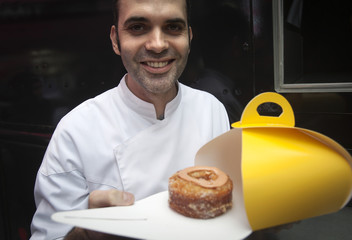 Celebrity baker Dominique Ansel, creator of the cronut, poses for a photo during a publicity event in Times Square in New York