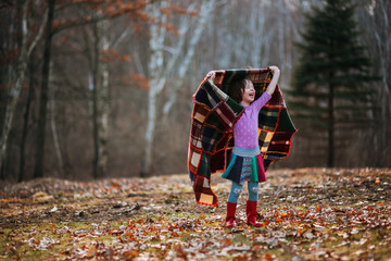 Girl holding a blanket spinning around