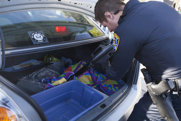 A San Diego police officer removes a 22 caliber rifle from the back of a car during a gun buy-back in San Diego.