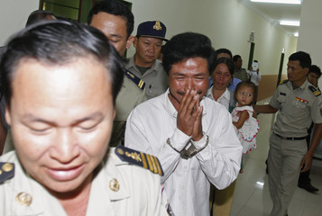 Oeun is escorted by police officers as his wife and his daughter cry at the Appeal Court in central Phnom Penh
