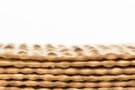 Stack of Passover matzah, edge view. Isolated on white. Copy space.