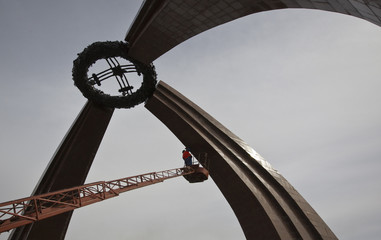A worker, lifted by a bucket truck, cleans a World War Two monument in the Kyrgyz capital Bishkek